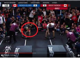 Screen cap of Patrick Vellner violating rule during dumbbell snatch