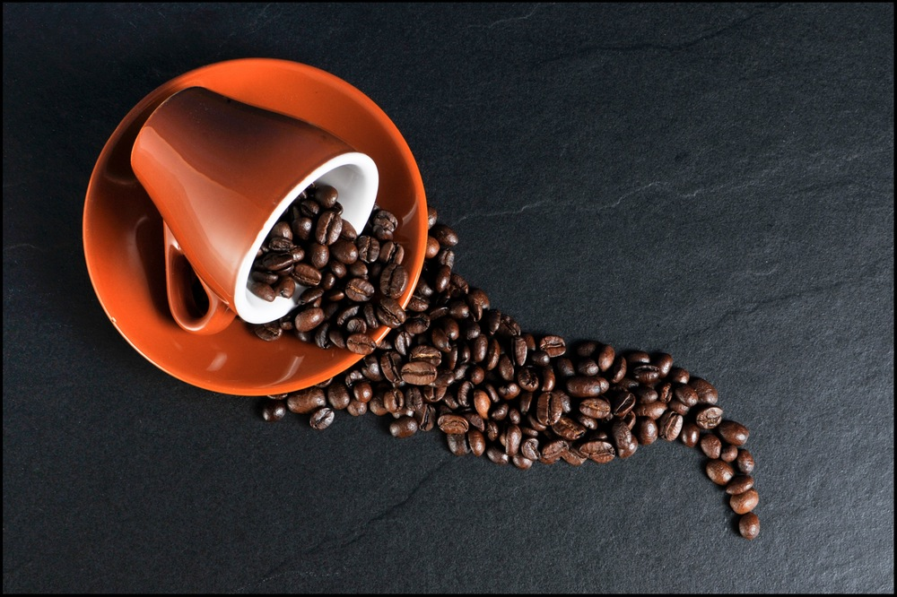 coffee beans spilled out of coffee cup