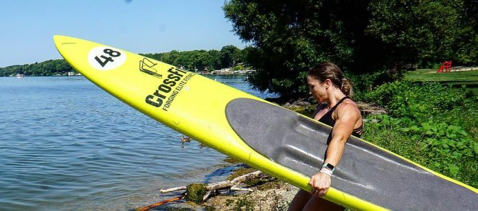 Demo Team member McKenzie Flinchum heads into the water to test the paddleboard event.