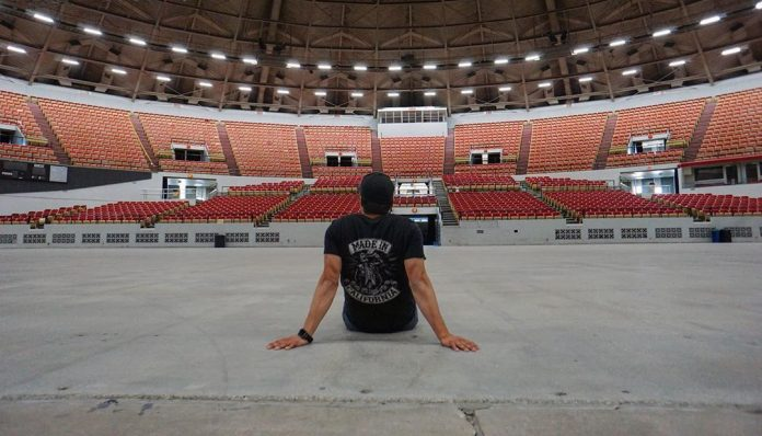 Dave Castro sitting in the Coliseum of the Alliant Energy Center in Madison, Wisconsin. Photo via Instagram, @thedavecastro